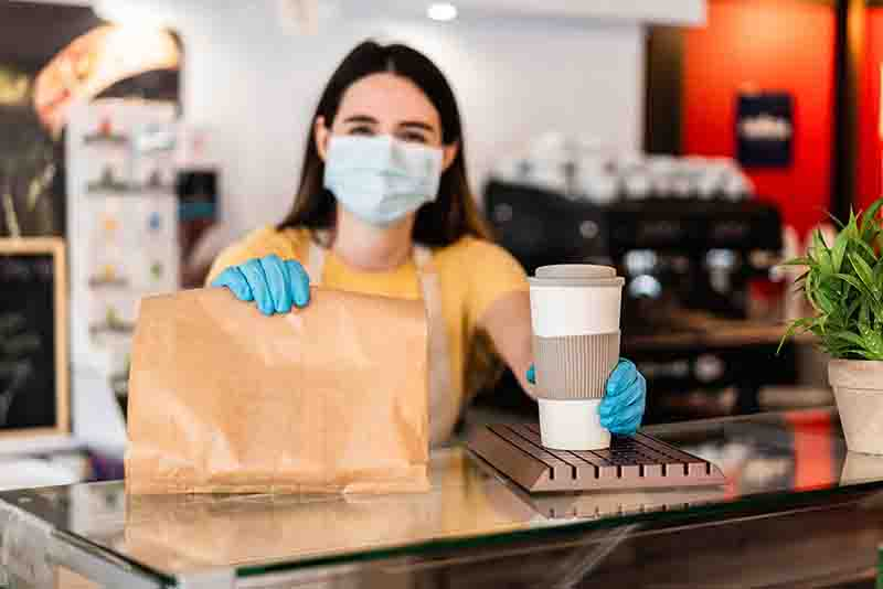 Young woman wearing face mask while serving takeaway breakfast and coffee inside cafeteria restaurant - Worker preparing healthy food inside cafè bar during coronavirus period - Focus on right hand